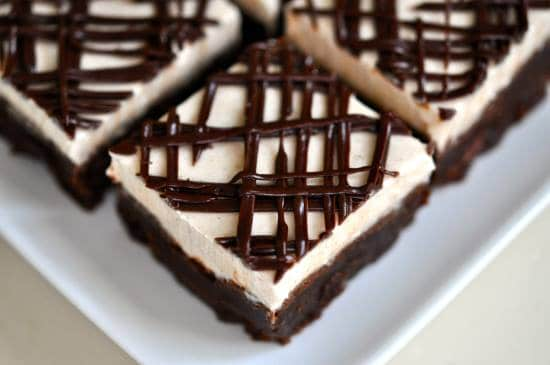 close up of a white plate of cut brownies with creamy topping and chocolate drizzle