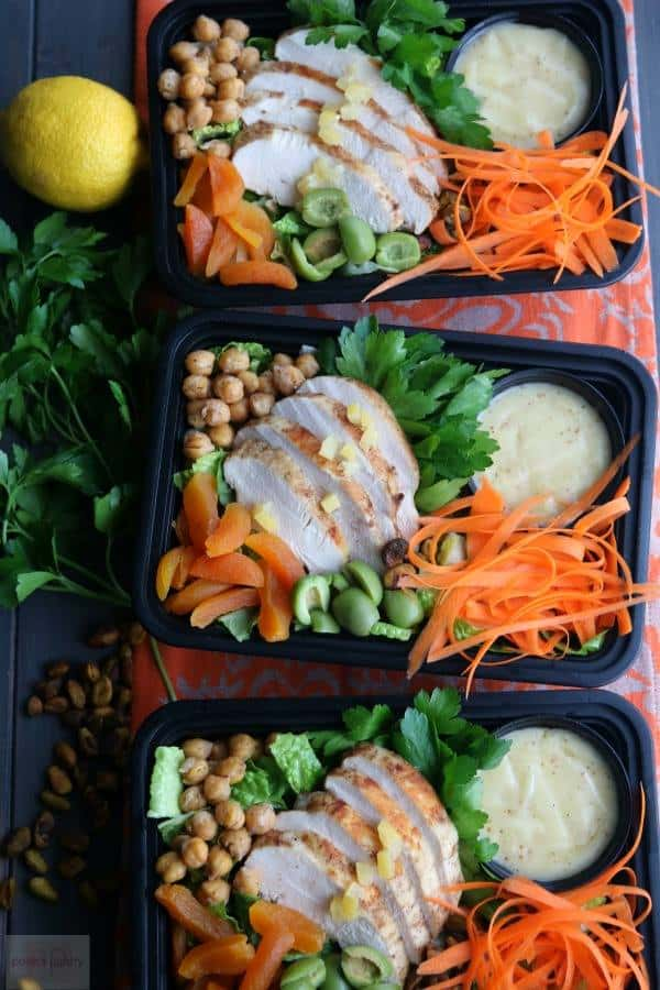 overhead shot of 3 containers with greens shredded carrots, apricots, olives, sliced chicken breast and chickpeas