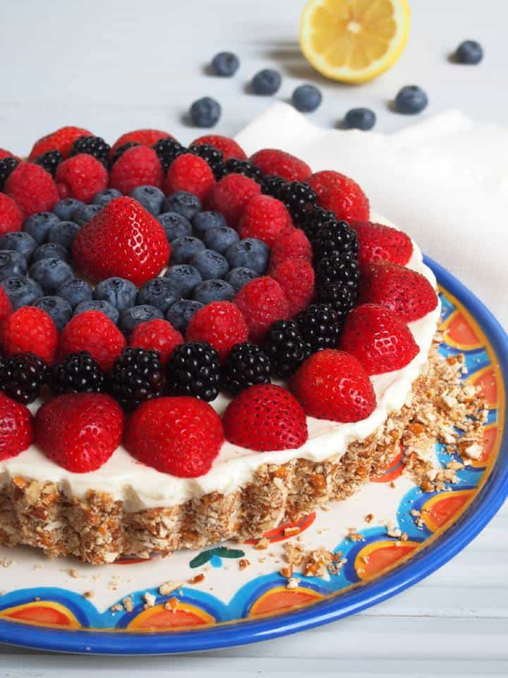 a lemon tart on a white, blue and orange platter topped with strawberries, raspberries, blackberries, and blueberries