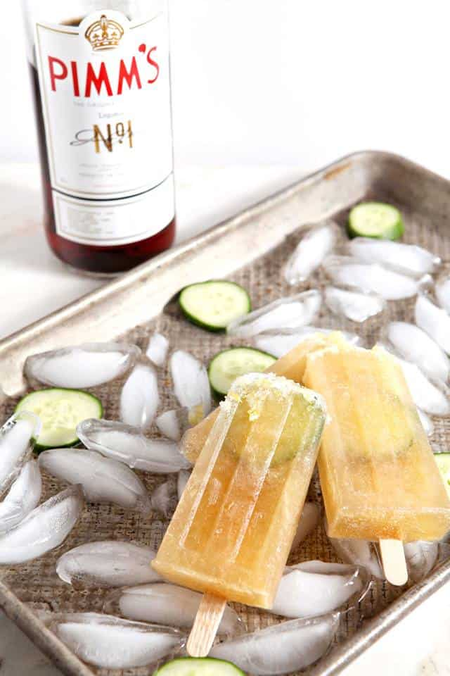 baking sheet covered with ice cubes and cucumber slices with two popsicle and a bottle of Pimm's in the background