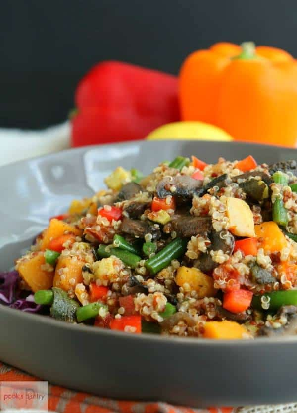closeup of a gray dish piled with quinoa with diced vegetables with a red and orange sweet pepper in the background