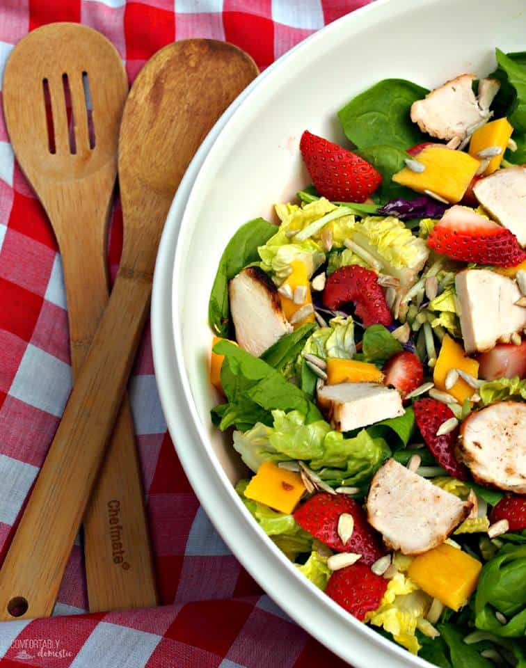 overhead shot of white bowl full of greens, diced chicken, diced mango and sliced strawberries on a red and white checked tablecloth with wooden salad servers