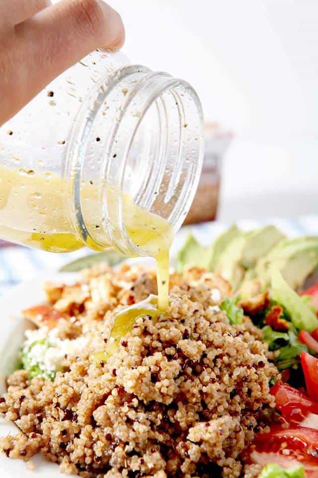 close up of bowl of quinoa, avocado, and tomato with salad dressing being poured over