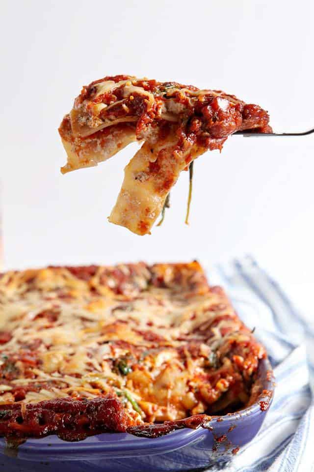 a bite of spinach lasagna held up on a fork with the casserole of lasagna at the bottom