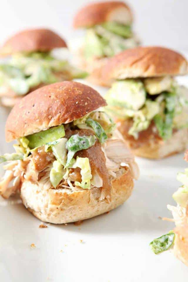 close up of small shredded chicken sandwiches on buns