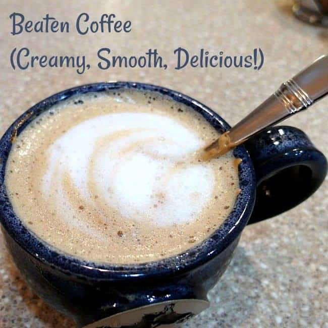 closeup of a mug of creamy foamy coffee with a spoon in it. Text reads: beaten coffee (creamy, smooth, delicious)
