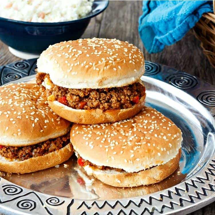 three sloppy joe sandwiches on sesame seed buns on a silver platter