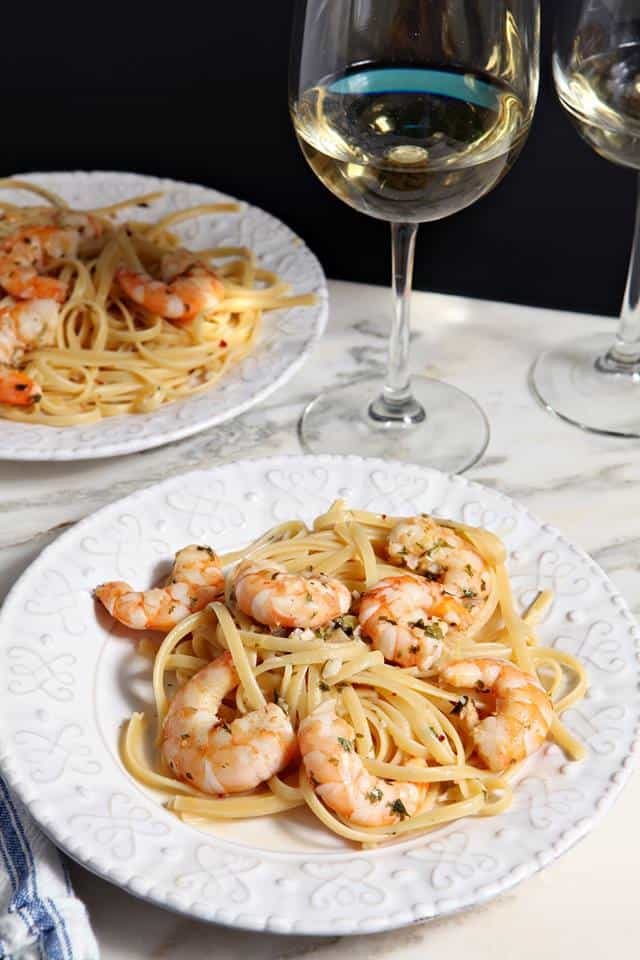lemon shrimp pasta on a plate with a glass of wine