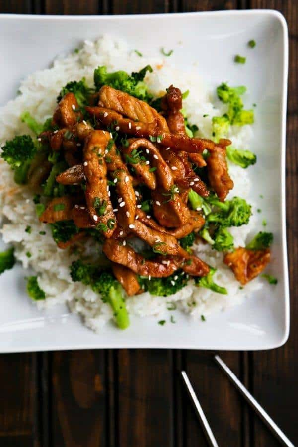 overhead shot of strips of cooked meat and broccoli over rice on a square plate
