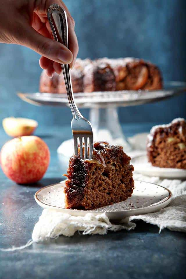 vertical image with a whole Bundt cake on a cake stand in the background and a cut slice on a white plate with a person sticking a fork in it to get a bite