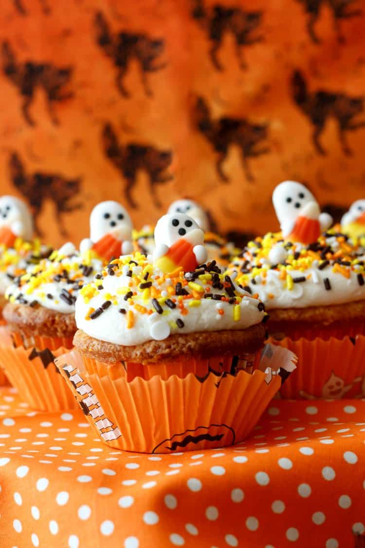 candy corn cupcakes with ghost toppers on an orange background
