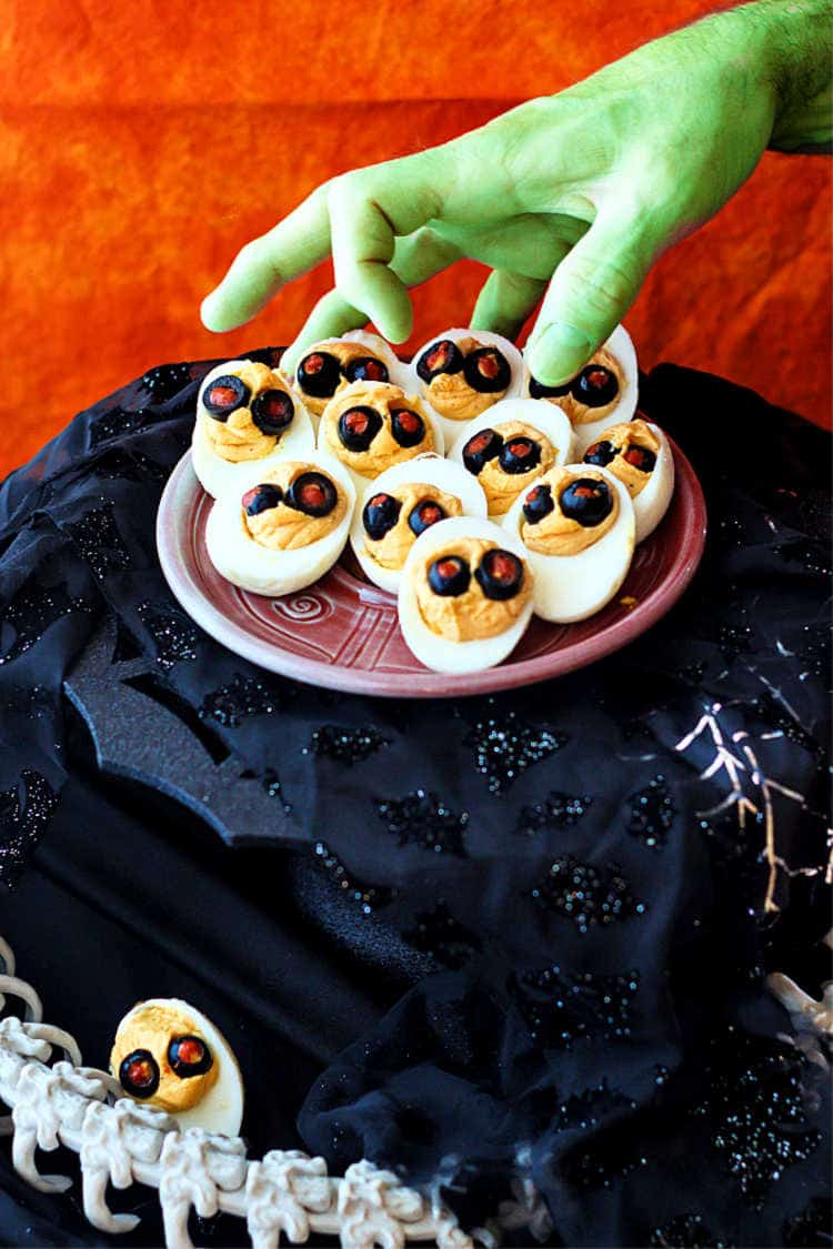 a platter of devilish Halloween deviled eggs on a black spider web pedestal with a green hand reaching for one