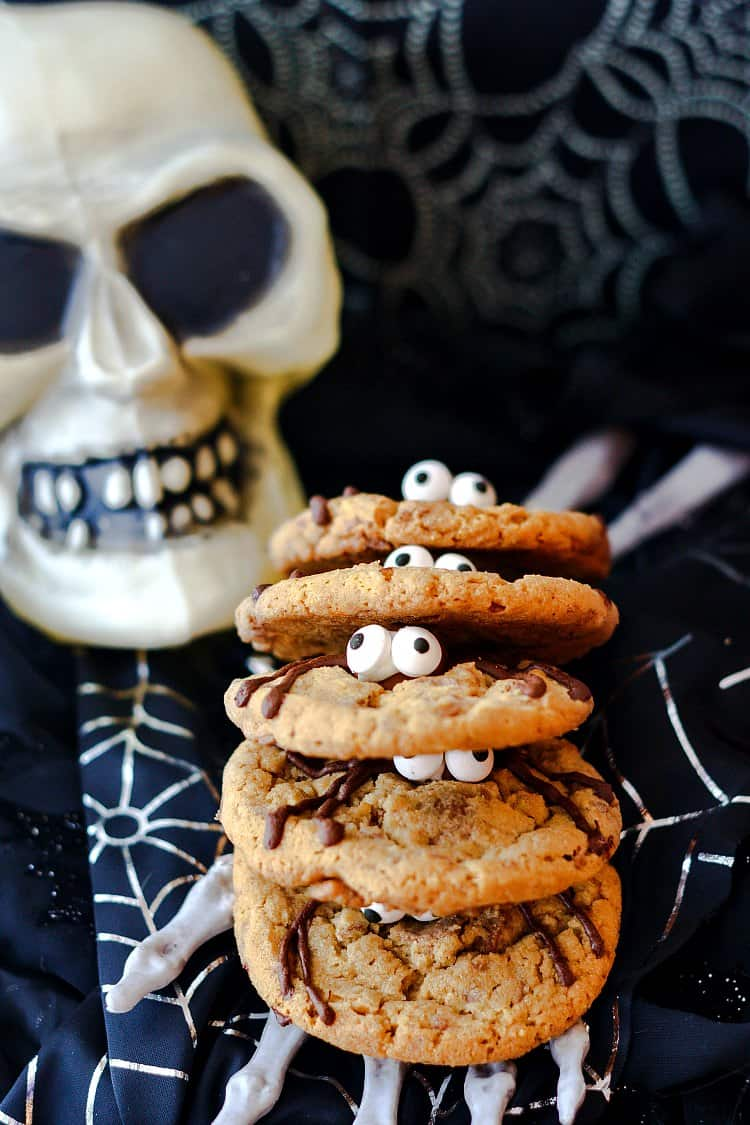 A stack of spider cookies with their googly eyes peering out.