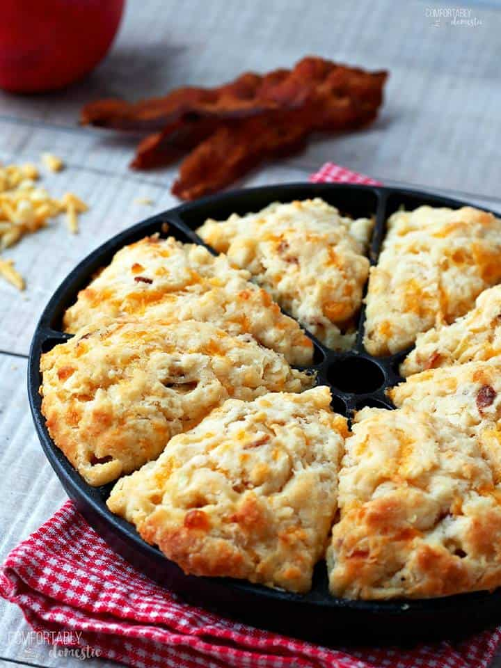 sectioned cast iron pan with baked scones with shredded cheese and cooked bacon in the background