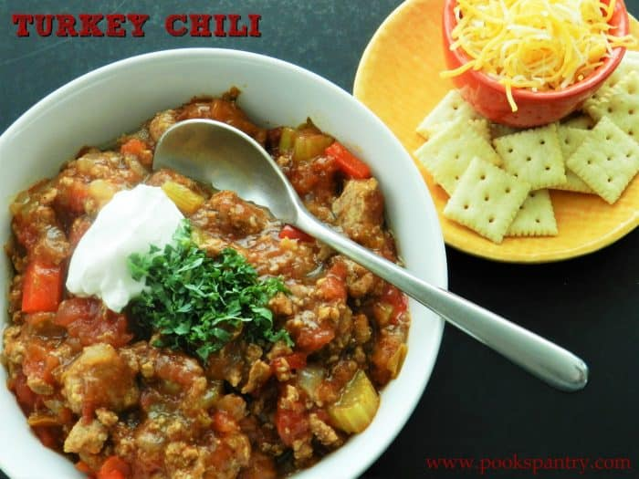 a bowl of turkey chili with cheese, sour cream, and crackers