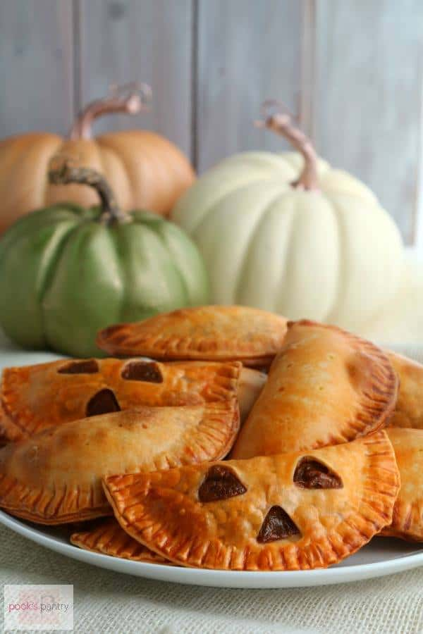 plate of baked empanadas with three small triangles of each cut out so they look like jack o'lanterns with small decorative pumpkins in the background