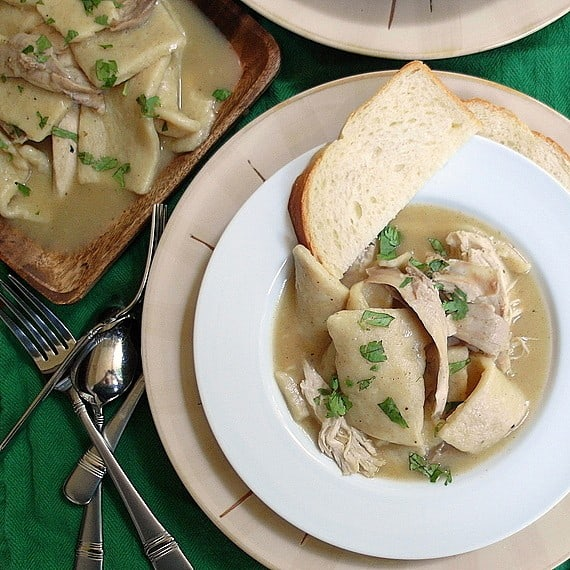 overhead shot of chicken and dumplings served with white bread