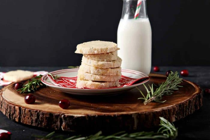 stack of ginger rosemary shortbread cookies on a plate with a bottle of milk