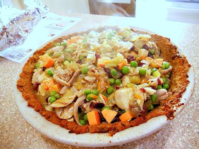 leftover turkey shepherd's pie with stuffing crust filled with turkey gravy sweet potato cubes, peas and craisins