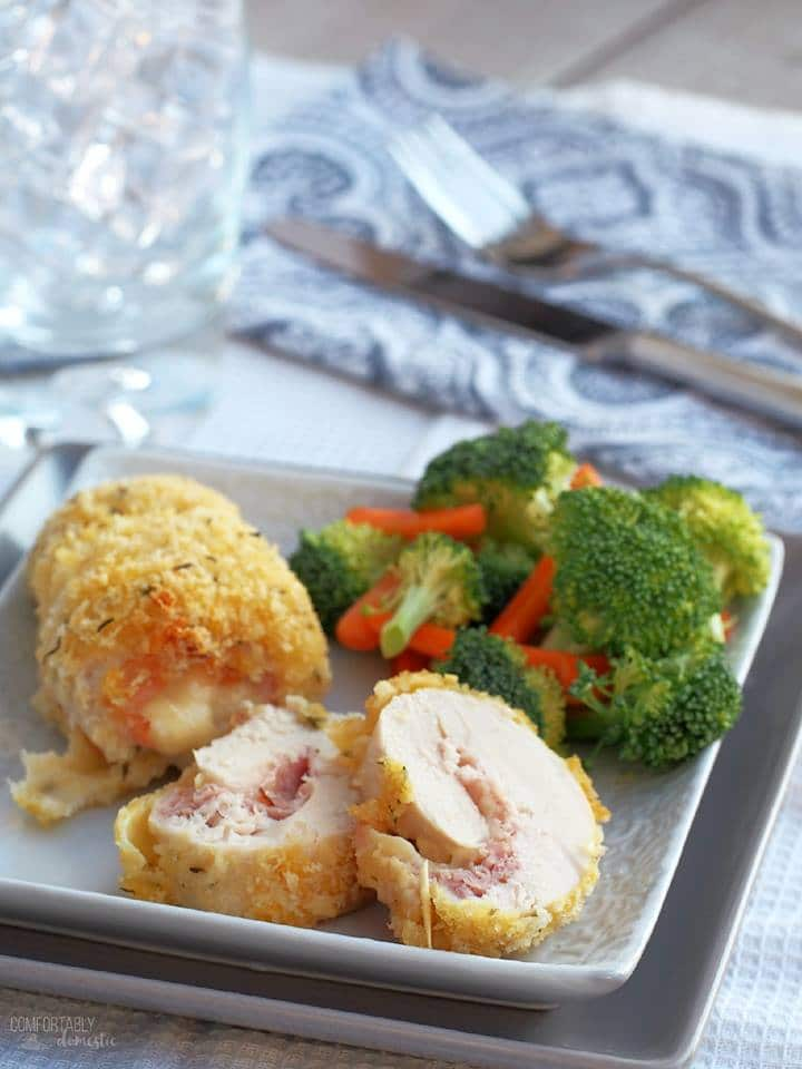 chicken rolled around ham and cheese and baked on a square white plate with broccoli