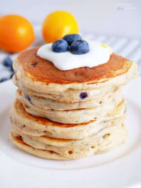 stack of blueberry protein pancakes topped with cream and blueberries