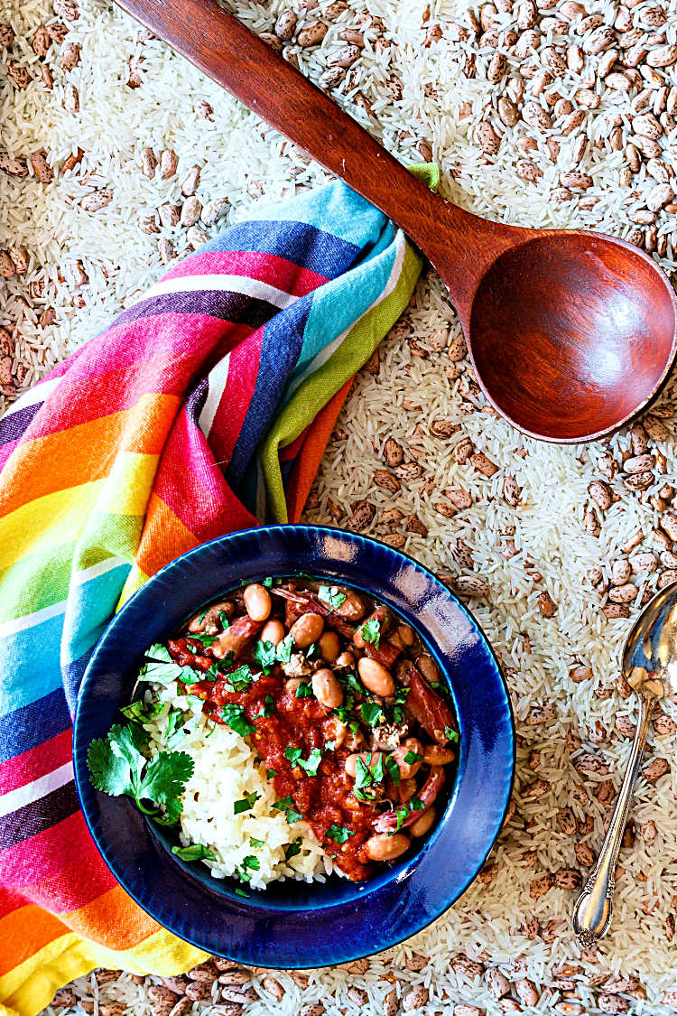 overhead shot of a wide-rimmed blue bowl with rice and beans, topped with salsa on a background of dried rice and beans with a ladle, napkin and spoon