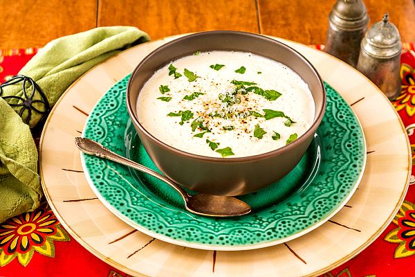 bowl of cream of cauliflower soup on a green plate with napkin and salt and pepper shakers