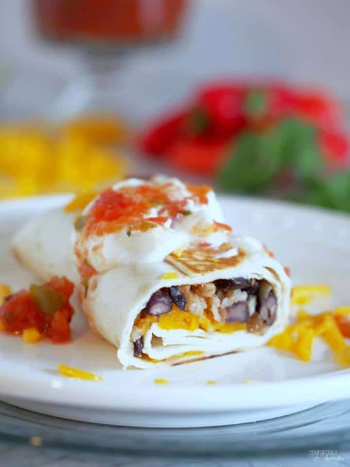 half a black bean and cheddar cheese burrito on a white plate and topped with sour cream and salsa