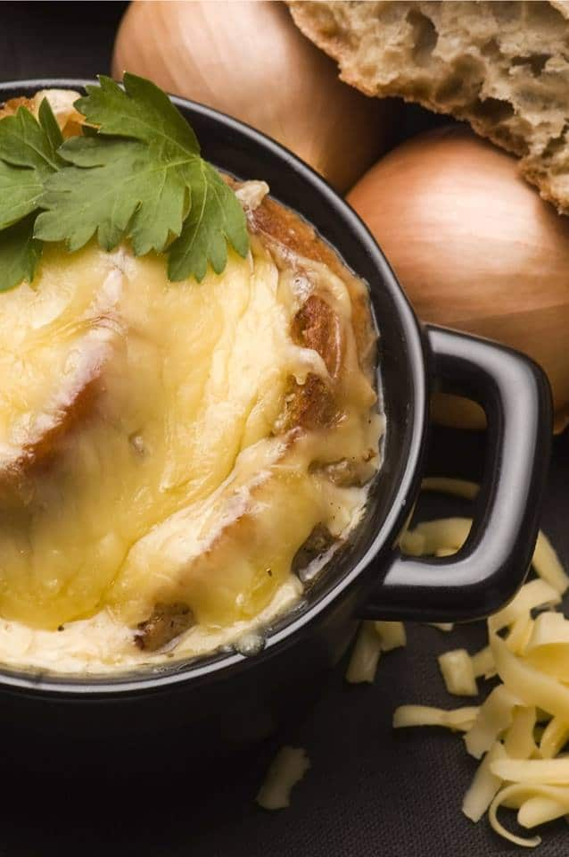 overhead shot of bowl of French onion soup topped with toasted bread and lots of melted cheese