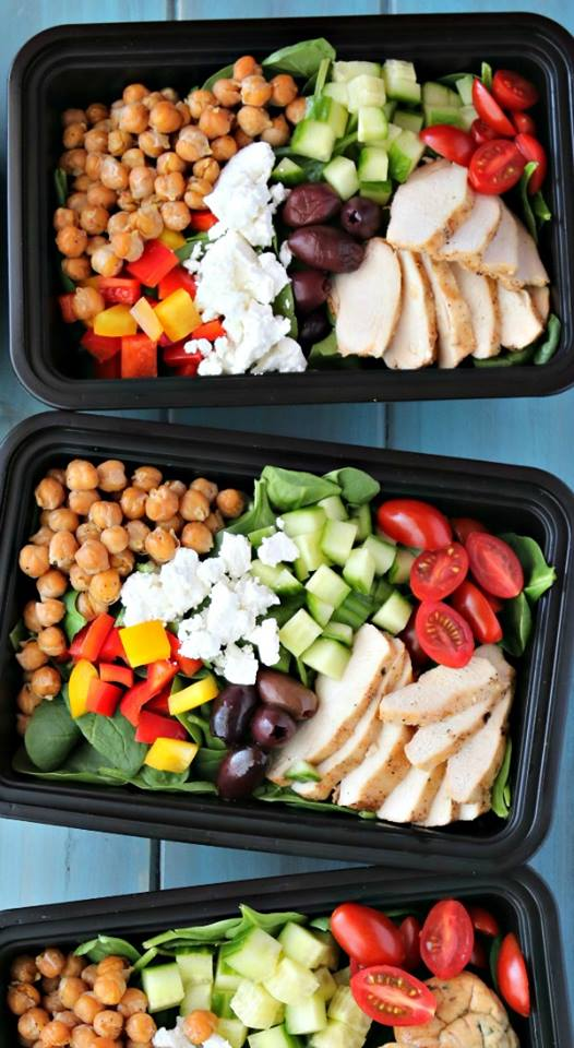 3 black containers with chickpeas, chicken, feta, olives, tomatoes, cucumber, spinach, and sweet peppers