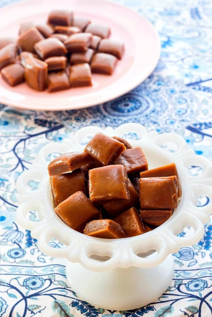 square pieces of butterscotch candy in a white candy dish and on a pink plate