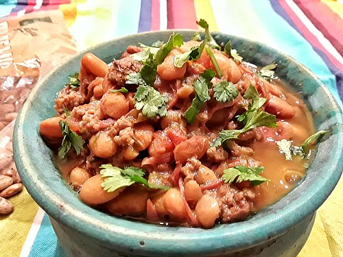 close up of soupy pinto beans in a blue bowl topped with chopped cilantro