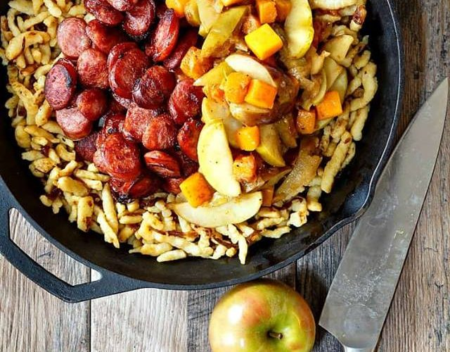 overhead shot of a skillet full of spaetzle topped with cooked Polish sausage and diced vegetables