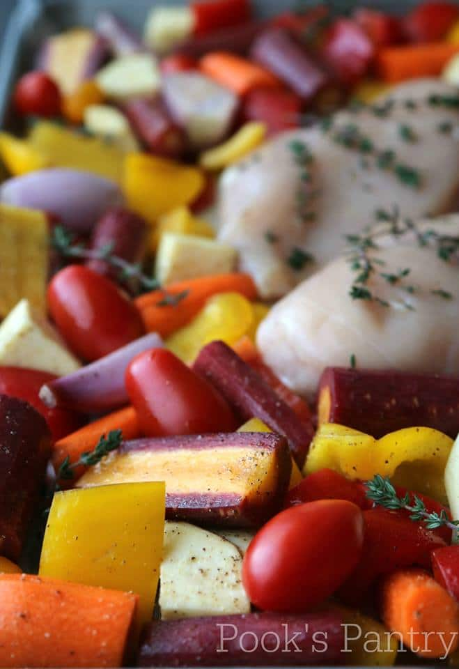 chicken breasts and cut vegetables on a sheet tray