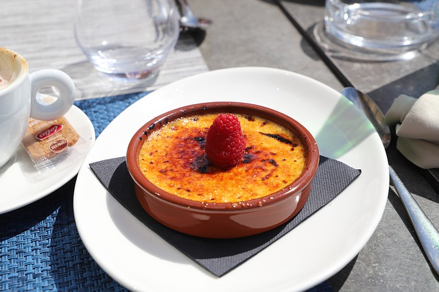 a shallow terra cotta ramekin on a white plate with creme brulee and a raspberry on top