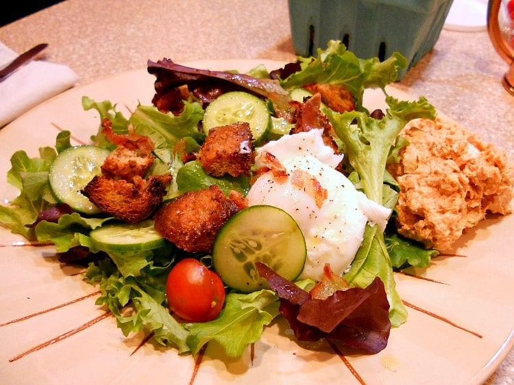plate of salad with lettuce, cucumbers, crumbled bacon, poached egg, and croutons made from spent grain bread.