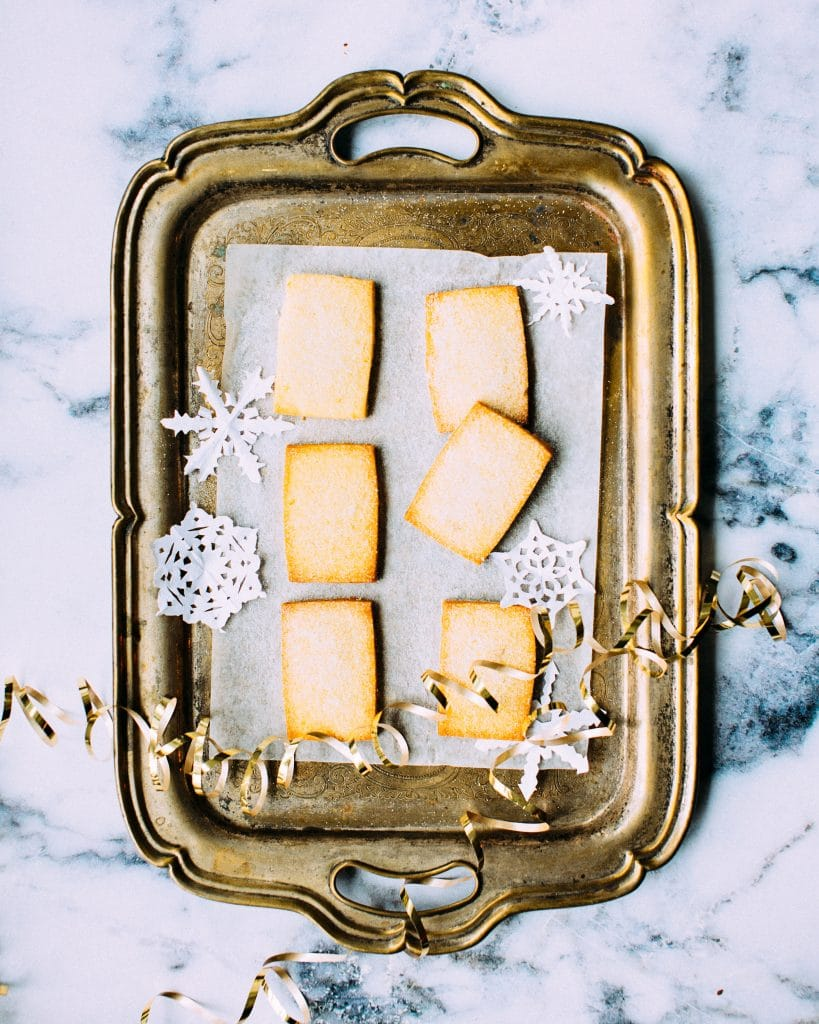 overhead shot of rectangular sable dough cookies on parchment on a tarnished silver tray.