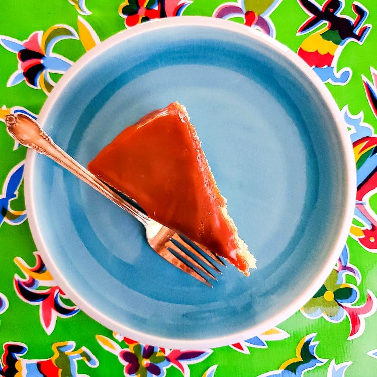 overhead shot of an upright slice of cake with butterscotch glaze on a blue plate on a green print tablecloth