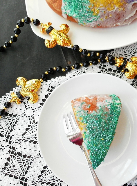 vertical image of a slice of mardi gras king cake on a white plate with gold fleur de lis beads
