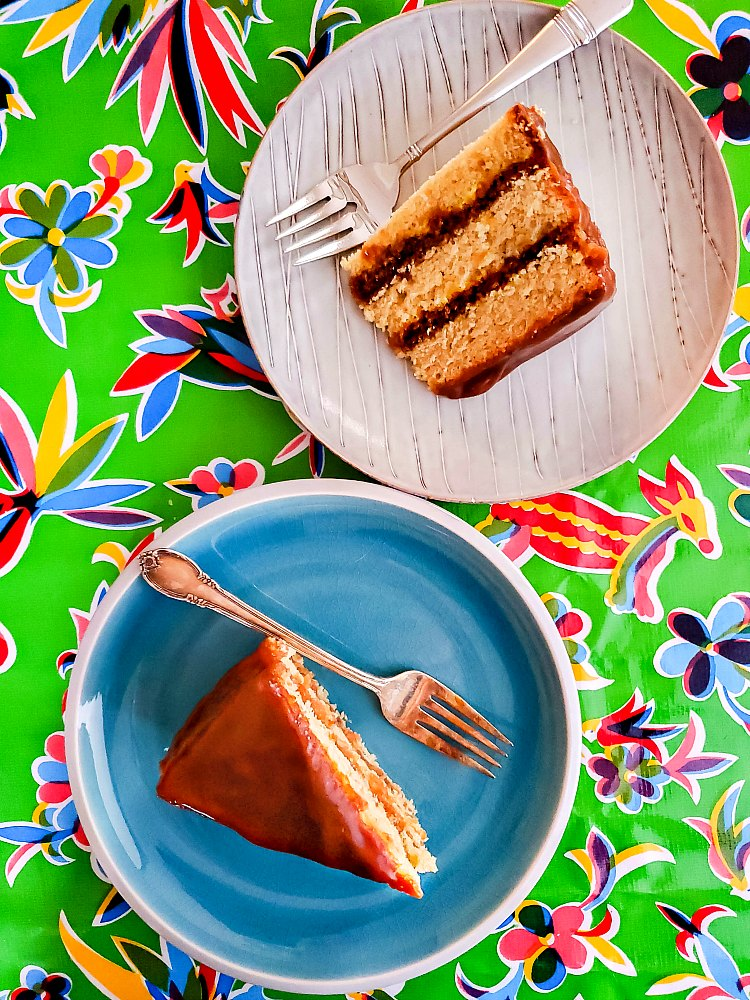overhead shot of two plates with slices of cake on them on a green print background