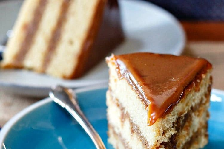 slice of golden 3 layer cake with caramel colored icing
