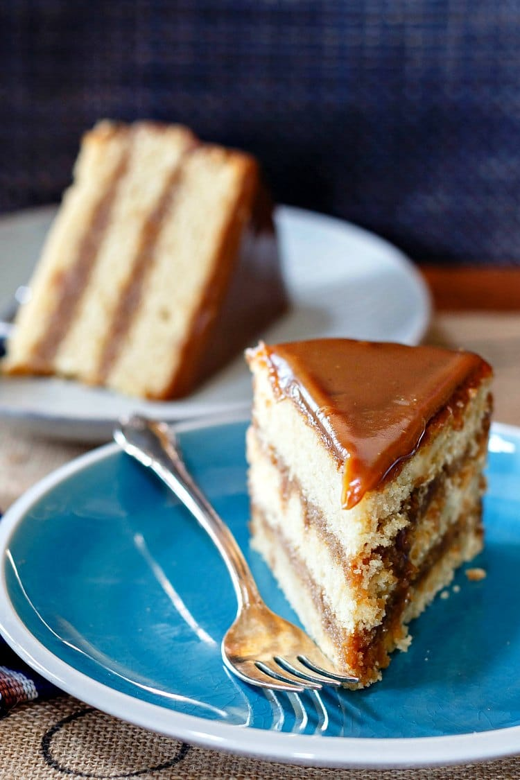 3 layer slice of butterscotch cake upright on a blue plate with a slice of the same cake on its side in the background