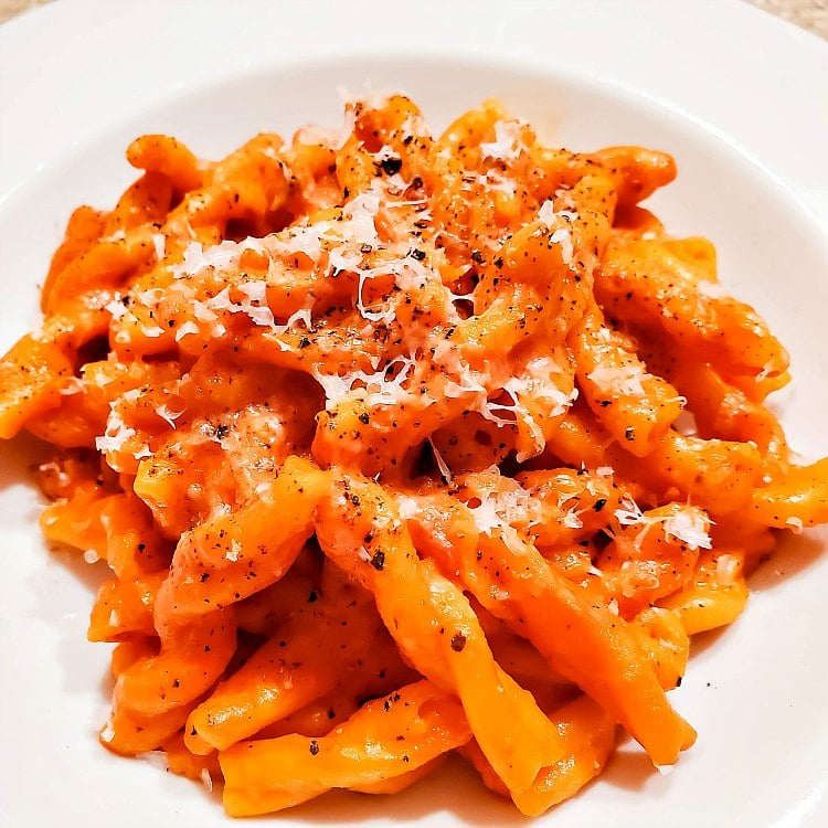 a plate of rotini pasta coated in sauce and topped with Parmesan cheese and black pepper