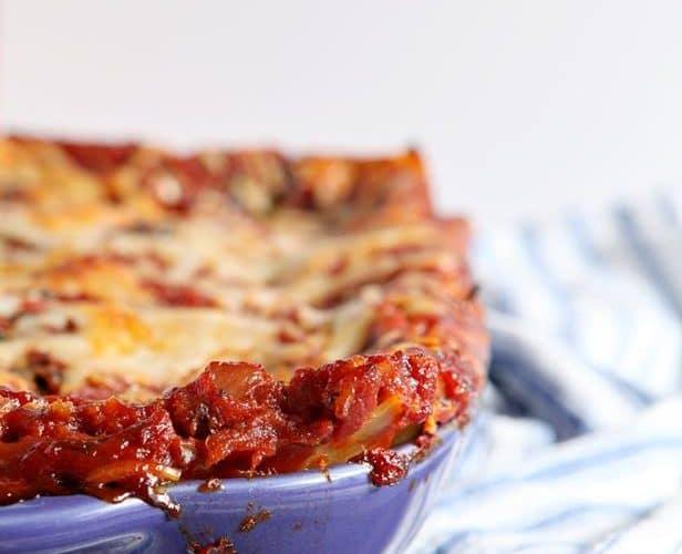 vertical image of vegetarian lasagna in a blue baking dish