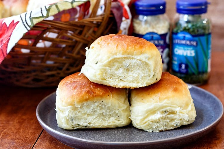3 potato rolls on a plate with glass jars of freeze dried garlic and chives in the background