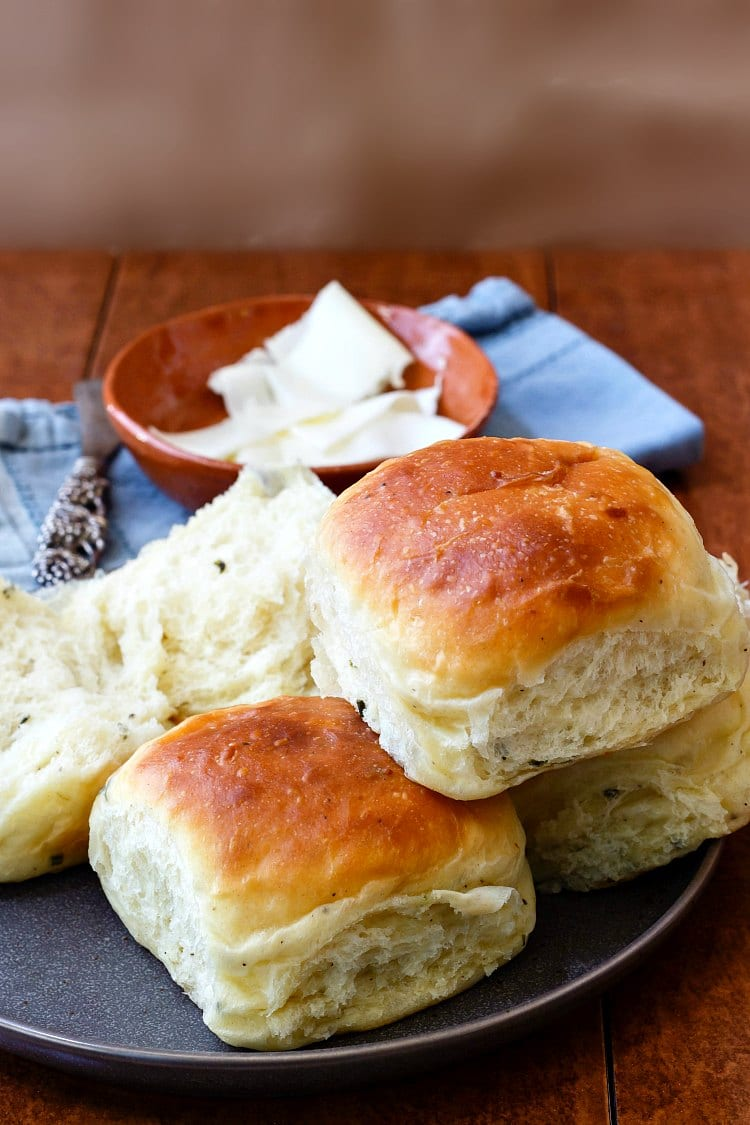 a stack of three soft dinner rolls on a gray plate with one split dinner roll and butter in the background