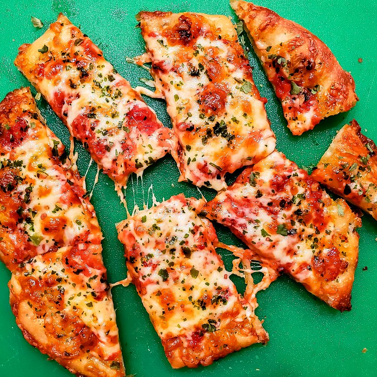 overhead shot of a small pizza cut in half and then crosswise into 8 slices on a green cutting board