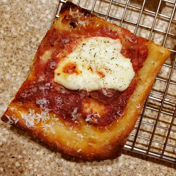 close up shot of one rectangular corner piece of grandma pizza topped with ricotta cheese and tomato sauce