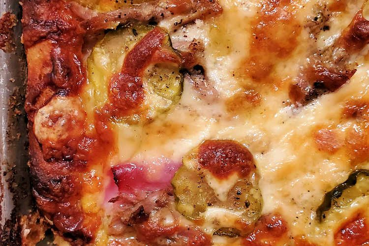 close up image of a baked cubano pizza shot from above