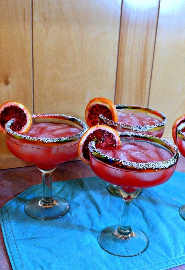 4 large cocktails in margarita glasses with salt on the rim and garnished with sliced blood orange